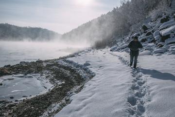 Russia, Amur Oblast, man walking at riverside of Bureya in snow-covered nature