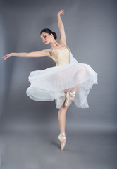 Beautiful slim woman ballet dancer in studio isolated on gray