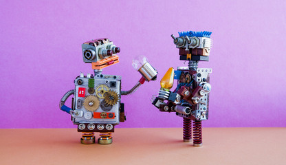 Robots communication, artificial intelligence concept. Two robotic characters with light bulbs. Creative design toys on pink wall, brown floor background.
