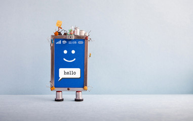 Friendly mobile smartphone gadget on gray background. Creative design touch screen phone device, light bulb capacitors sim card. Sms message Hello, smiley face on blue. Copy space