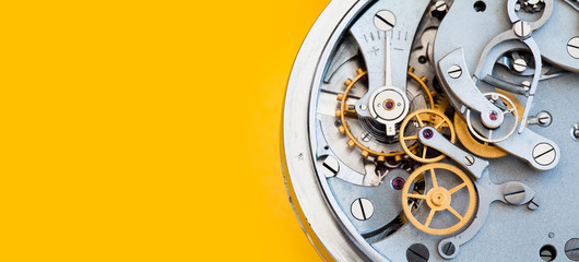Mechanic stopwatch chronometer mechanism, spring bronze cogs wheels macro view. Shallow depth of field, selective focus. Yellow colorful background. Copy space