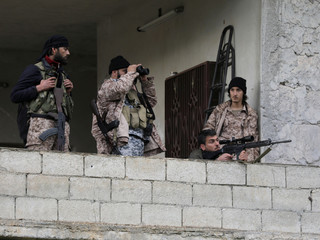 Turkish-backed Free Syrian Army fighter looks through binoculars in the north east of Afrin