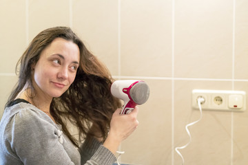 Young woman with brown hair drying hair with electric blowdryer at home