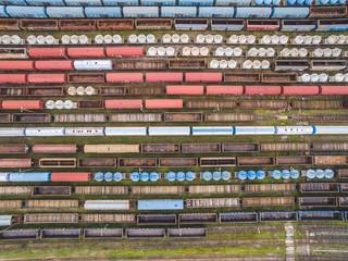 Wagony kolejowe widziane z lotu ptaka. Wagony ustawione w szeregi. Kolorowe linie i wzory utworzone przez wagony kolejowe.