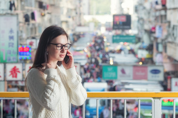 Young attractive caucasian brunette woman in eyeglasses standing on pedestrian footbridge and talking mobile phone. Blurred traditional Hong Kong street market as background.