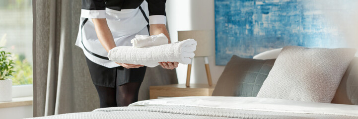 Panorama of housemaid putting towels
