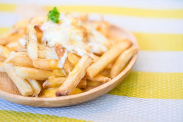French Fries with Melted Cheese on wood bowl. Closeup of french fries with cheese.selective focus