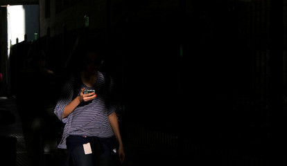 A woman uses her mobile phone as she walks on a street in Buenos Aires