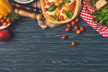 top view of appetizing tasty pizza and scattered cherry tomatoes on table