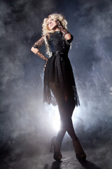 luxurious blonde with a fluffy white long hair and long legs posing in a short black lace dress on a dark stage background in the smoke with the light