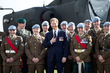 Britain's Prince Harry poses for a photograph in front of an apache helicopter with some of the latest graduates who have received their Wings at the Army Aviation Centre in Middle Wallop