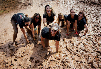Women go through an obstacle course during the Mud Run event in Tel Aviv