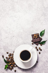 Black coffee in white cup, chocolate and coffee beans in glass jar on concrete background. Top view, space for text.