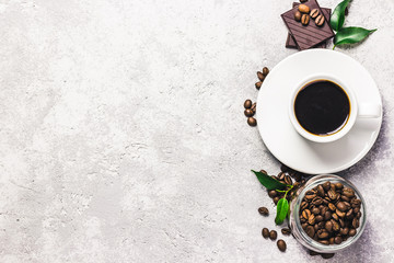 Black strong coffee in white cup, dark chocolate on concrete background. Top view, space for text.