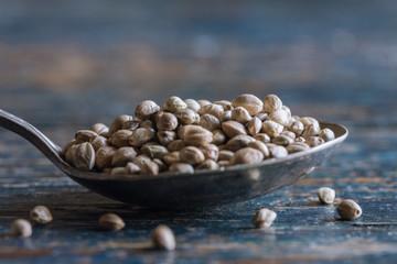 Whole hemp seeds on vintage spoon