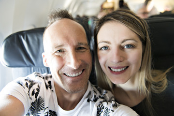 A couple selfie and smile happily in airplane