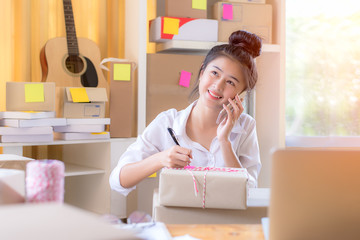 Asian smiling young women writing order from customer online for preparing package product.  Lifestyle for working at home.