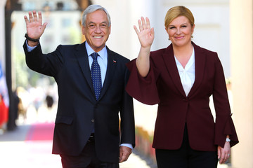 Chile's President Pinera and Croatia's President Kolinda Grabar-Kitarovic wave to the media at the government house in Santiago