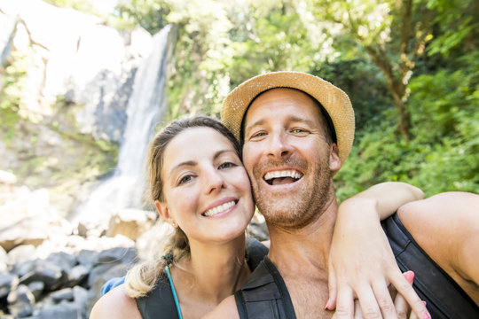 Happy couple taking selfie portrait at tropical waterfalls in summer vacation