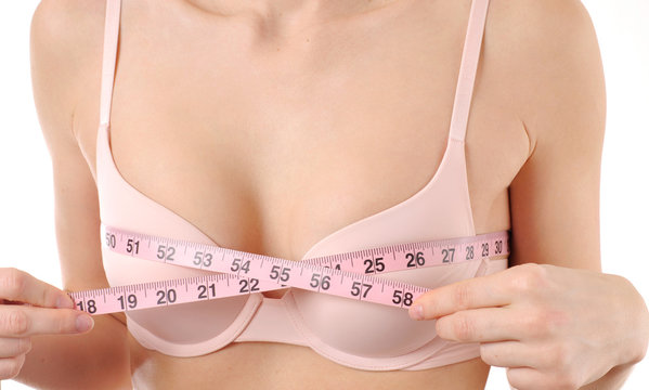 Perfect chest in pink bra. Woman measures her breast
