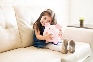 Lovely little girl with her piggy bank at home