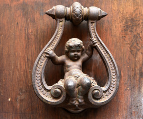 Türklopfer an einer braunen Holztür in der Altstadt von Rom