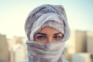 Muslim woman wearing traditional Arabic clothing outdoors.