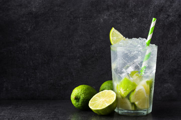Caipirinha cocktail in glass on black stone. Copyspace