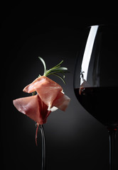 Glass of red wine with prosciutto and rosemary.