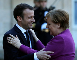 French President Emmanuel Macron welcomes German Chancellor Angela Merkel as she arrives for a meeting at the Elysee Palace in Paris