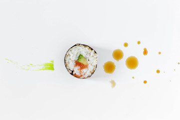 Sushi roll with splashes of soy sauce and brush strokes of wasabi. Concept design.  Japanese cuisine