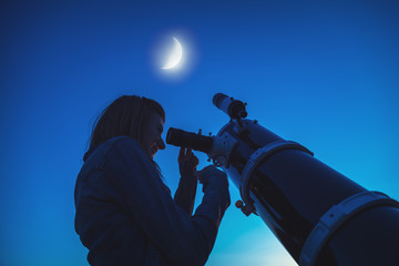Silhouette of a girl and telescope with Moon on the sky.