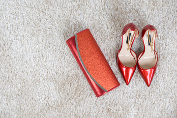 Red high heel women shoes and wallet on synthetic cream fur texture with copy space. Flat lay