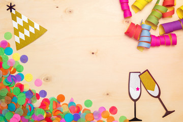 Colorful confetti, streamer and party hat on wooden background from above