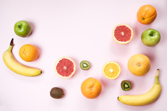 Colorful fresh fruit on Gray table. Orange, banana, apples, kiwi, grapefruit. Flat lay, top view, copy space. Fruit background.