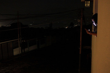 A girl uses her cell phone at the window of her house during a blackout in San Cristobal