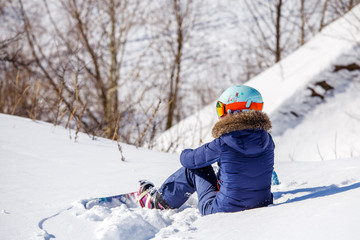 Photo from back of athlete in helmet sitting on snowy slope