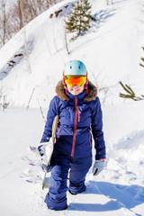 Image of female athlete wearing helmet with snowboard