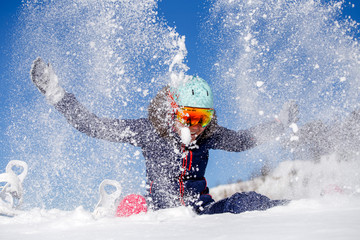 Picture of athlete woman sitting in snowdrift , throws snow