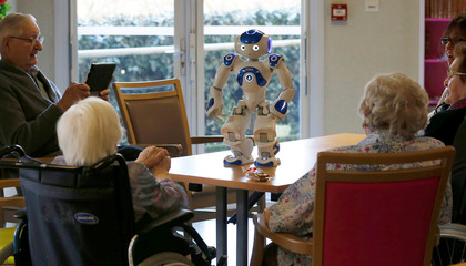Elderly people play with a robot named NAO, manufactured by Softbank Robotics, in their retirement home in Bordeaux