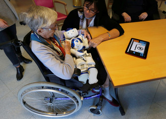 An elderly woman plays with a robot named NAO, manufactured by Softbank Robotics, in her retirement home in Bordeaux
