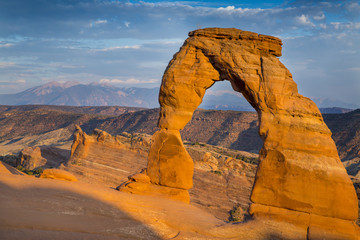 Golden evening light illuminates Delicate Arch just before sunset across the spectacular landscape near Moab, Utah.