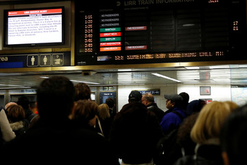 People stand in Pennsylvania Station waiting for trains in the Manhattan borough of New York City