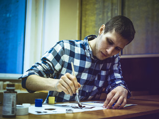 young artist drawing a picture with brush sitting at the table