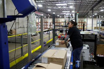Toys 'R' Us vendor Learning Resources worker moves a box on a conveyor belt at the warehouse in Vernon Hills