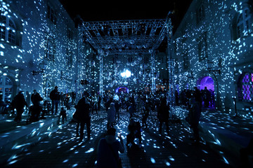 People are walking in a light installation during the Festival of Lights in Zagreb