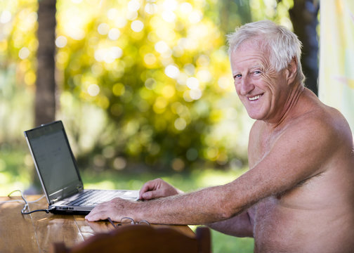 Portrait of senior man working with laptop in outdoor without shirt