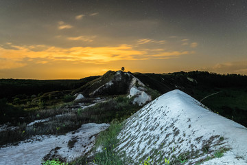 Night glowing sky over the chalk hills. Natural archaeological monument - Krapivenskoye ancient settlement, Belgorod region, Russia.