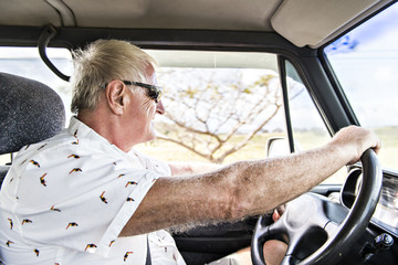 mature senior man on his car drive on tropical country