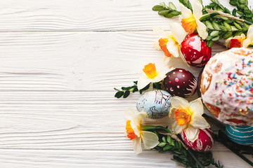 happy Easter concept. stylish painted eggs and easter cake on rustic wooden background with spring flowers, top view. seasons greeting card. space for text. modern flat lay